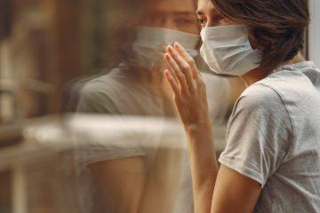 Mujer con máscara médica parada junto a la ventana